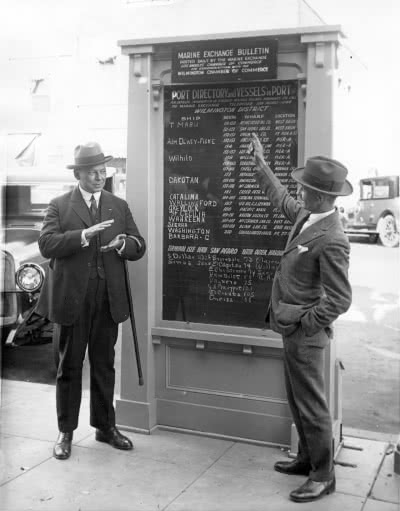 two men standing in front of a chart of ship arrivals circa 1930
